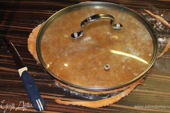 Достаем корж из духовки и пока теплый ровняем края по крышке (или большой тарелке) с помощью ножа.