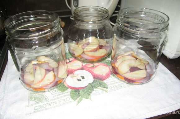 Банки моем. Крышки заливаем кипяченной водой, кипятим 5 минут. Овощи чистим и нарезаем колечками яблоко разрезаем, удаляем сердцевину с семенами и нарезаем дольками. Овощи и яблоко раскладываем по банкам.