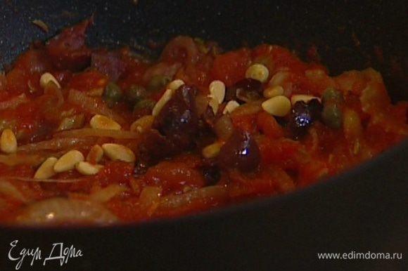 Сковороду с томатным соусом снять с огня, добавить оливки, каперсы, половину кедровых орехов, перемешать.