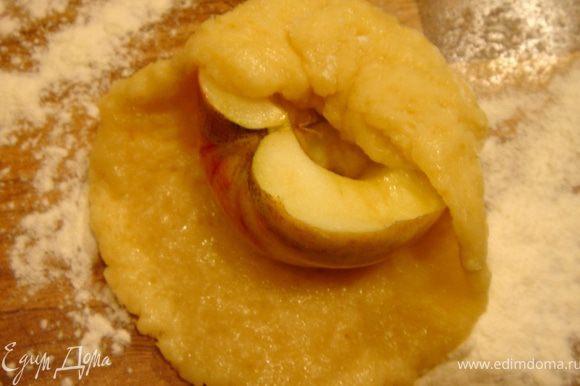 Тесто разделить на 12 частей(если фрукты крупные,то разделите тесто на своё усмотрение). Раскатайте каждую часть в лепёшку,сверху положите половинку яблока,срезом вверх.В выемку в яблоке можно разместить орех.Соберите края лепёшки вокруг яблока.