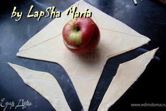 Из теста делаем два квадратика, в центр которых кладем по яблоку. С каждого края вырезаем треугольники как на фото.