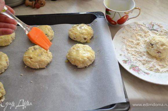 Из теста сформировать небольшие лепешки и каждый обвалять в муке. Выложить сырники на противень. Смазать вторым желтком.