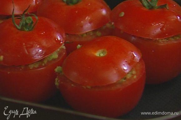 Наполнить помидоры хлебной начинкой, уложить их в небольшой противень, накрыть «крышечками» и отправить в разогретую духовку на 15–20 минут.