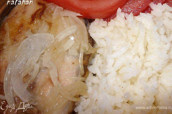В порционную тарелку положить кусочек рыбы с луком, а рядом рис и помидоры. Приятного аппетита!