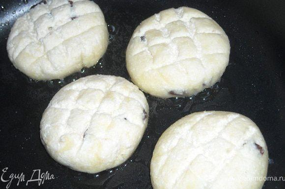 Мокрыми руками сформировать шарик из творожной массы (примерно 1 ст. ложка), хорошо обвалять его в муке, слегка приплюснуть и жарить на сковороде с толстым дном, на медленном огне, под крышкой, с небольшим количеством масла.