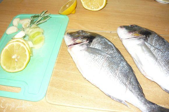 Рыбу помыть, почистить, выпотрошить. Сделать неглубокие надрезы вдоль хребта - такие, чтобы поместились пластинки чеснока. По бока сделать по 3-4 неглубоких надреза. Сбрызнуть лимонным соком.