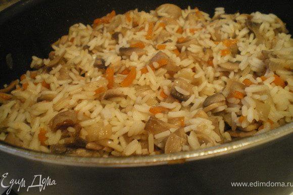Шампиньоны отварить. Затем обжарить, добавить морковь и мелко нарезанный лук. Посолить. Тушить 15 минут. Засыпать рис, добавить грибной бульон и тушить до готовности риса.