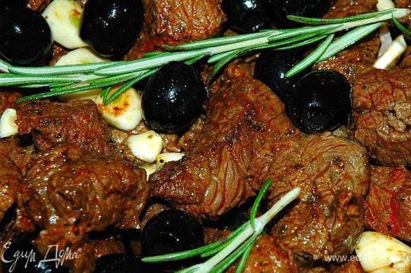 Теперь нам надо очень быстро, но порционно обжарить кусочки нашей говядины на раскаленной сковороде или гриле без масла, буквально 2-3 минуты. Обжаренное мясо выкладываем в наш сотейник поверх овощей. Теперь добавим маслины, рубленый чеснок и веточки свежего розмарина. Перемешивать содержимое никак нельзя! Просто ставим наш сотейник на плиту и вливаем в него бутылку белого сухого вина. Выпариваем вино в течение 15 минут.