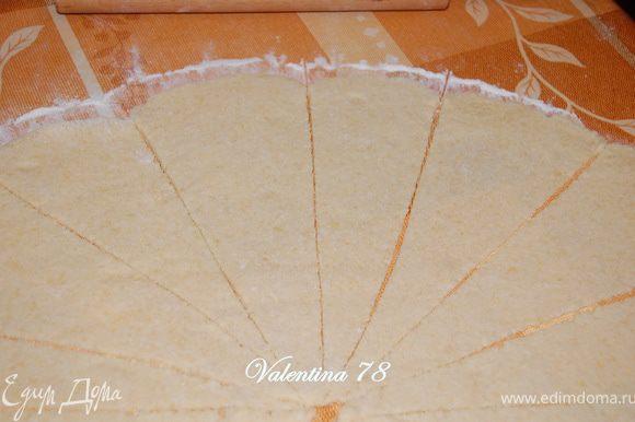 Тесто разделите на 2 части.Поверхность присыпать мукой, раскатать тесто в круг.Разрезать его на одинаковые треугольники