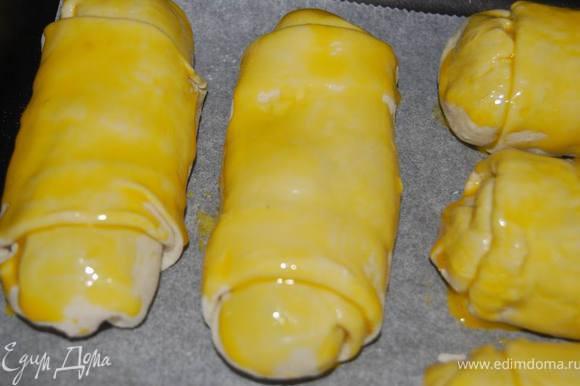 Выложить пирожки на противень с пергаментом, смазать желтком и выпекать 20 минут в разогретой до 200 градусов духовке.