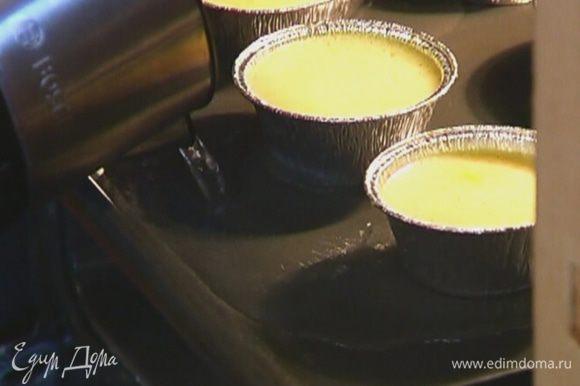 Противень поставить в разогретую духовку, задвинув не до конца, влить в него горячую воду на 1/3 высоты формочек.