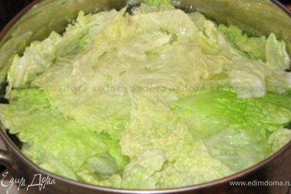 У листов савойской капусты вырезать центральную прожилку и опустить в кипящую воду на 3 минуты. Откинуть на дуршлаг. Оставить один половник воды от капусты.