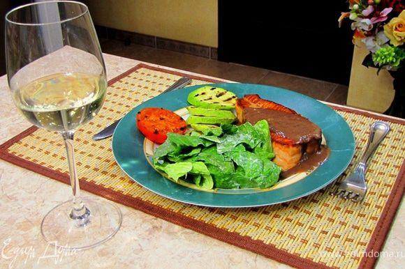 Выложите семгу на тарелку. Полейте сверху приготовленным соусом. Рядом положите заправленный салат, половинку помидора и жаренные кабачки.