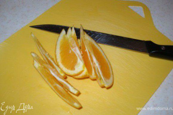 Нарезать половину апельсина тонкими дольками, а со второй половины выдавить сок и добавить к пуншу.