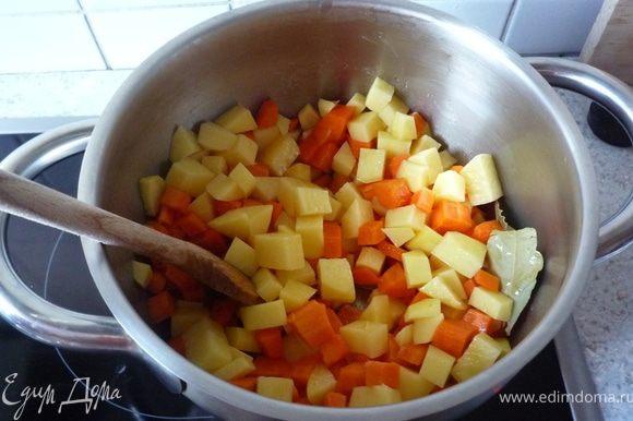 Лук почистить и мелко порезать. Картофель и морковь почистить, помыть и порезать на кусочки. Разогреть масло в кастрюле и обжарить лук, картофель, морковь. Добавить лавровый лист, влить овощной бульон, довести до кипения и под крышкой на умеренном огне тушить минут 15.