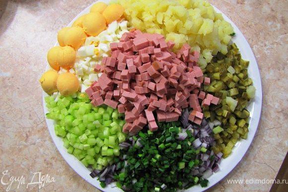 Порежьте все ингредиенты на одинаковые кусочки, включая репчатый лук. Огурец лучше всего почистить. Яйца можете нарезать без желтков, а затем раскрошить желтки в салат. Порежьте мелко петрушку.