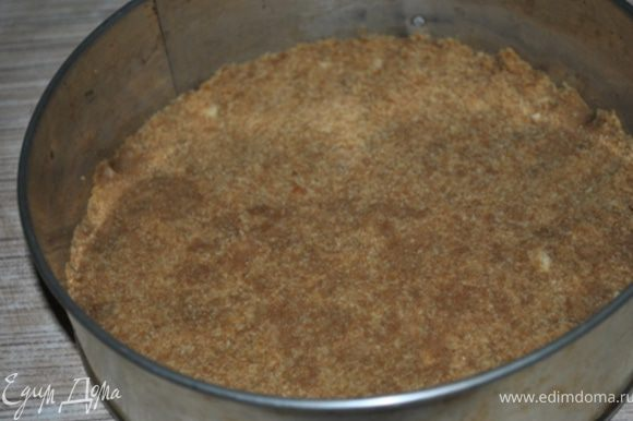 Печенье размолоть, смешать с растопленным маслом. Полученную смесь выложить на дно формы 22 см. Выпекать при 180 гр. 10 минут.