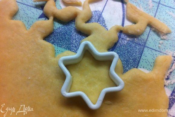 Специальной формочкой вырежи звезды.Вырезай их как можно ближе друг к другу.Оставшееся тесто скатай в шар и снова раскатай при помощи скалки.