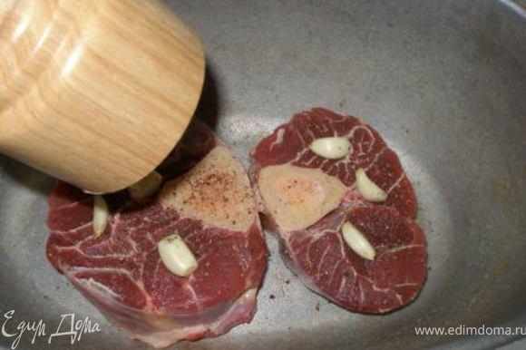 Мясо выложить в жаропрочную посуду, посолить, поперчить. Сверху выложить целые зубчики чеснока.