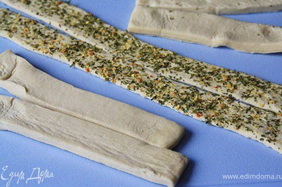 Тесто нарезать на полоски по количеству крабовых палочек. Раскатать тесто по длине на пряной смеси, чтобы она осталась на тесте.