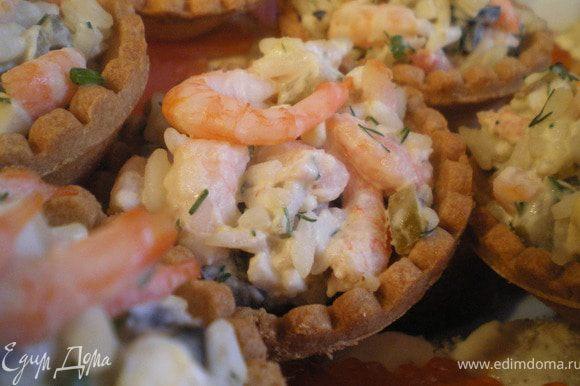 Наполнить тарталетки приготовленным салатом, украсить зеленью и креветками.