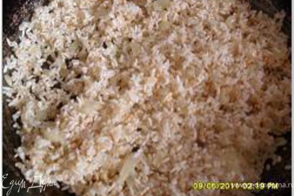 Лук порезать. Прокалить масло в сковороде/сотейнике, добавить лук и рис и обжаривать до золотистого цвета