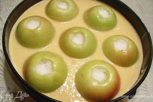 Выложить яблоки в глубокую форму для запекания, смазанную маслом. Между яблоками залить тесто. Выпекать в духовке 50 мин при 180℃.