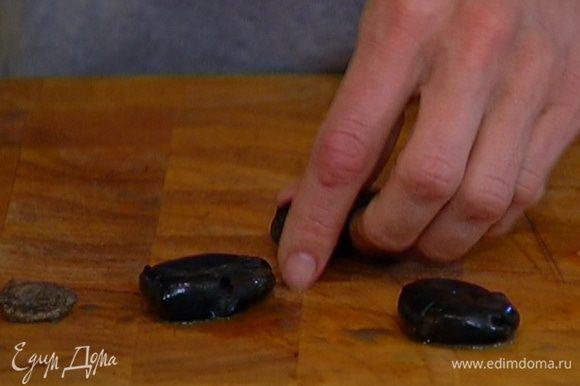 Оливки раздавить плоской стороной ножа и, удалив косточки, слегка измельчить руками.