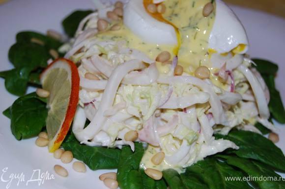 Посыпаем салат сверху горстью кедровых орехов, украшаем дольками лимона.