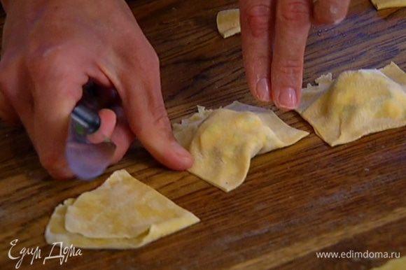 На одну половину теста поместить начинку, выкладывая ее горками по пол чайной ложки на некотором расстоянии друг от друга, накрыть второй половиной теста, влажными руками скрепить края и ножом разрезать тесто на квадратики с начинкой посередине. Если края у равиоли расходятся, скрепить их вручную.