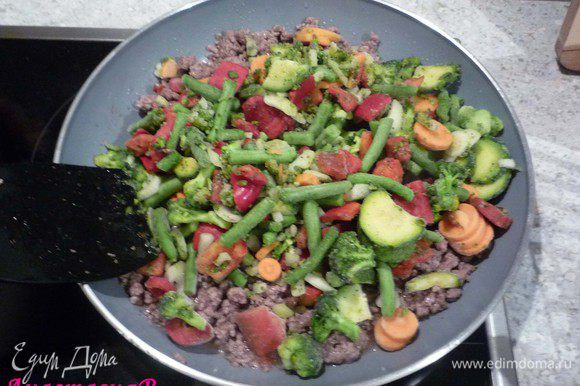 Добавить замороженные овощи и минут 5 все вместе обжарить.