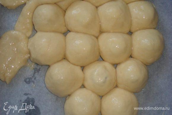 Уложить шарики на противень в виде грозди винограда и смазать взбитым яйцом.