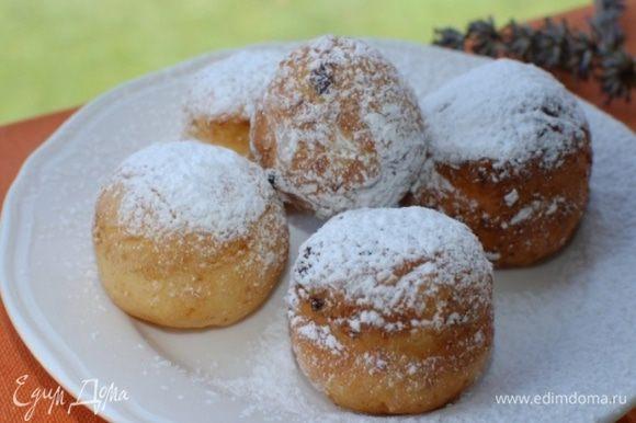 Готовые пончики выкладывать на бумажное полотенце, чтобы убрать излишки жира, затем переложить на блюдо и посыпать сахарной пудрой.
