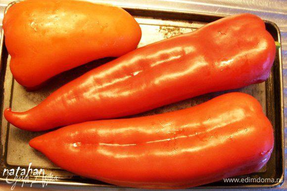 Перцы (у меня красные 2 шт. с острыми носиками и половинка с тупым носиком) помыть, обсушить и выложить на противень. Противень поставить в разогретую до 200 градусов духовку и запекать перцы 20 минут, периодически их переворачивая.