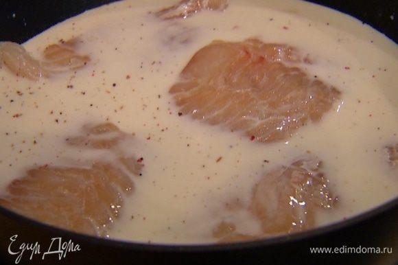 Молоко налить в глубокую сковороду, посолить, поперчить, добавить чеснок и выложить рыбу. Готовить 8–10 минут.