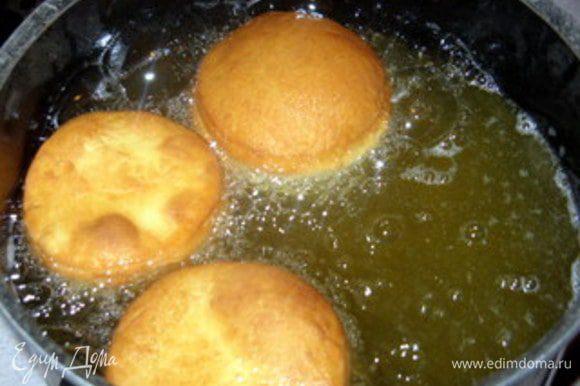 Нагреть арахисовое масло. Готовность масла проверить деревянной палочкой. Если вокруг неё образуются пузырьки, масло готово к жарке.(или проверить обрезком теста). Жарить по 2-3 пончика за раз, сначала с одной стороны, затем с другой, пока они не подрумянятся.