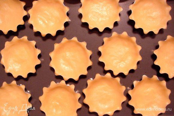 Разделить тесто на 16 кусочков и заполнить формы для корзиночек, равномерно распределив тесто руками. Форму смазывать не нужно, т.к. в тесте достаточно масла.