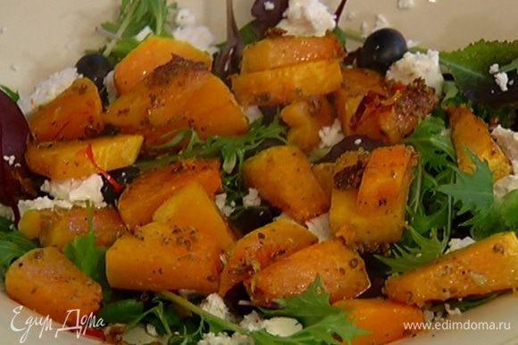 Салатный микс выложить на блюдо, посолить, поперчить, разложить часть оливок, сверху покрошить половину феты и выложить запеченную тыкву.