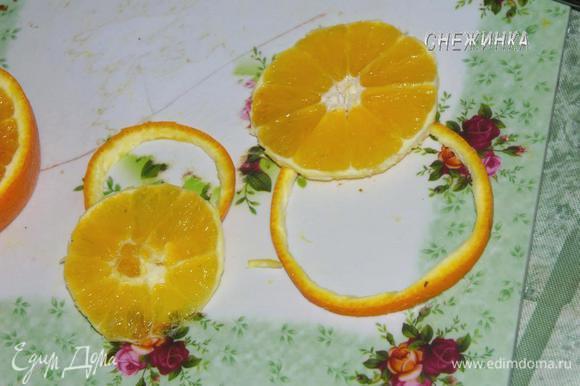 Для украшения используем половину апельсина и киви. Отрезаем два круга из апельсина, один больше, другой поменьше. Острым ножом отрезаем по окружности кожуру.