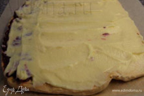 Готовый пласт теста необходимо остудить, снять пекарскую бумагу, нанести крем и ягодную начинку на нижнюю сторону пласта и свернуть рулетом.