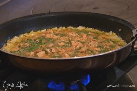 Добавить к яйцам тунец и зелень, перемешать и вылить в сковороду к луку.
