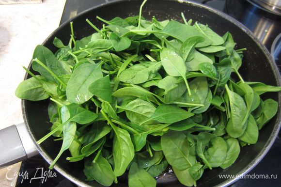 Поставьте снова сковороду на средний огонь. Налейте оливковое масло и высыпьте туда один пакет шпината. Сразу начните переворачивать листья. Они очень быстро потеряют объем. Когда уже будет позволять объем, высыпьте второй пакет шпината.