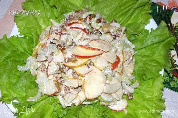 На плоское блюдо уложить листья салата, сверху положить заправленный салат и можно подавать.