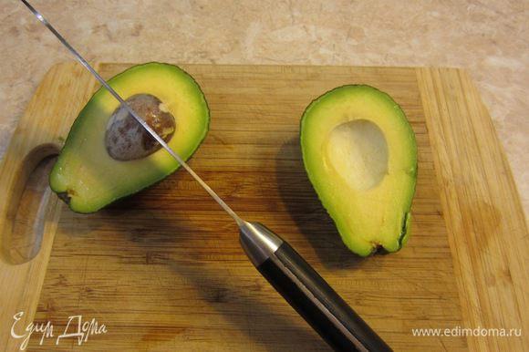 Прорежьте мякоть авокадо вокруг косточки. Покрутите одну половину авокадо по отношению к другой. Одна часть легко отделится от косточки. Осторожно ударьте лезвием по косточке. Лезвие воткнется. Поверните нож с косточкой и она отделится от мякоти.
