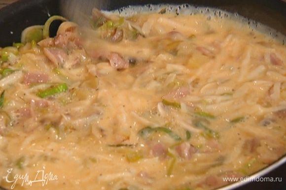 Вылить яично-сырную массу в сковороду, равномерно распределить и готовить на среднем огне.