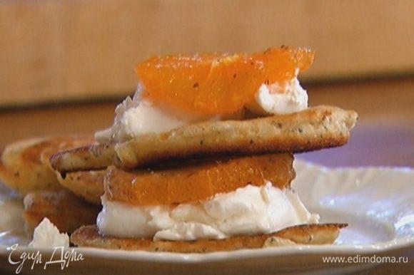 На половину всех оладий выложить по ложке сливочного сыра и по кружку мандарина, сверху поместить второй оладушек, немного сыра и кружок мандарина.