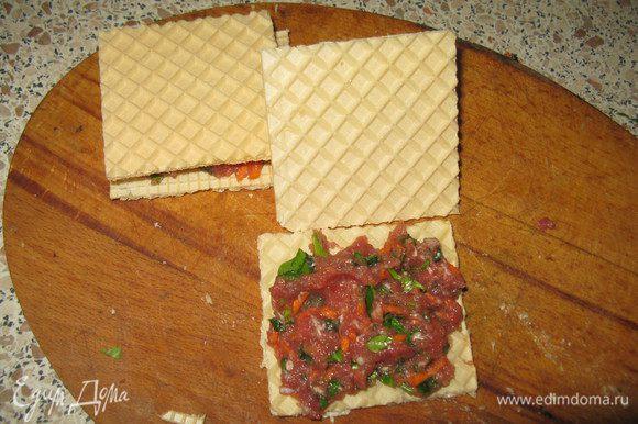 Вафельный корж разрезать на квадраты или треугольники.На одну часть положить фарш,накрыть второй.