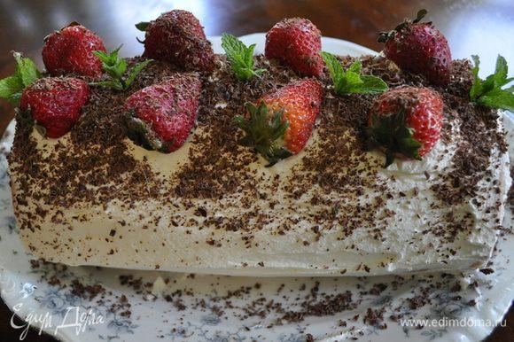 Переложить в сервировочное блюдо. Взбить один стакан сливок с добавлением 1 стол.л сах.пудры. Распределить лопаточкой поверх рулета-торта и украсить ягодами.