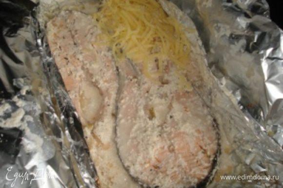 В это время натереть два вида сыра на терке и перемешать их. Спустя 30 минут, открыть фольгу, посыпать рыбу сыром и запекать еще 15 минут, но не закрывая уже фольгой.