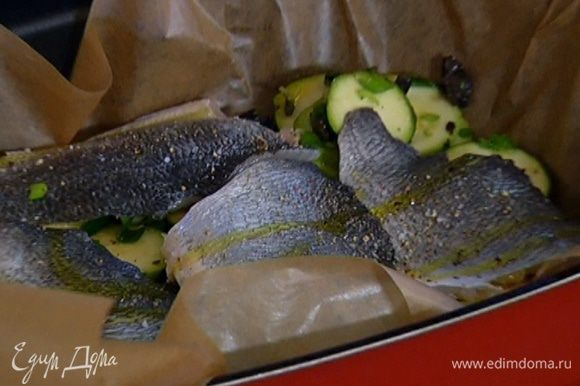Глубокий противень выстелить бумагой для выпечки, разложить овощи, затем выложить филе дорады кожей вверх, посолить, поперчить, сбрызнуть оставшимся оливковым маслом и полить белым вином.